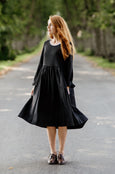 Woman wearing black smock dress with long sleeves, image from the front