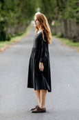 Woman wearing black smock dress with long sleeves, picture from the side