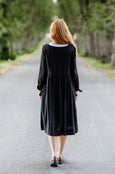 Woman wearing black smock dress with long sleeves, image from the back