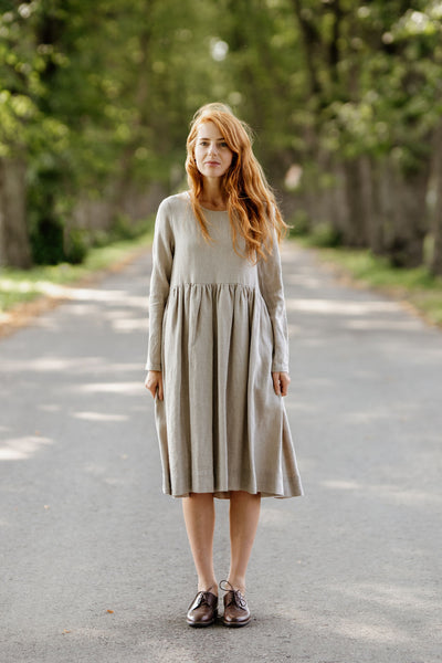 Woman wearing natural linen smock dress with long sleeves, picture from the front