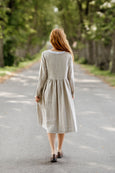 Woman wearing natural linen smock dress with long sleeves, picture from the back