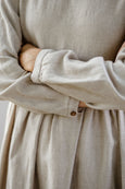 Woman wearing natural linen smock dress with long sleeves, up close image from the front