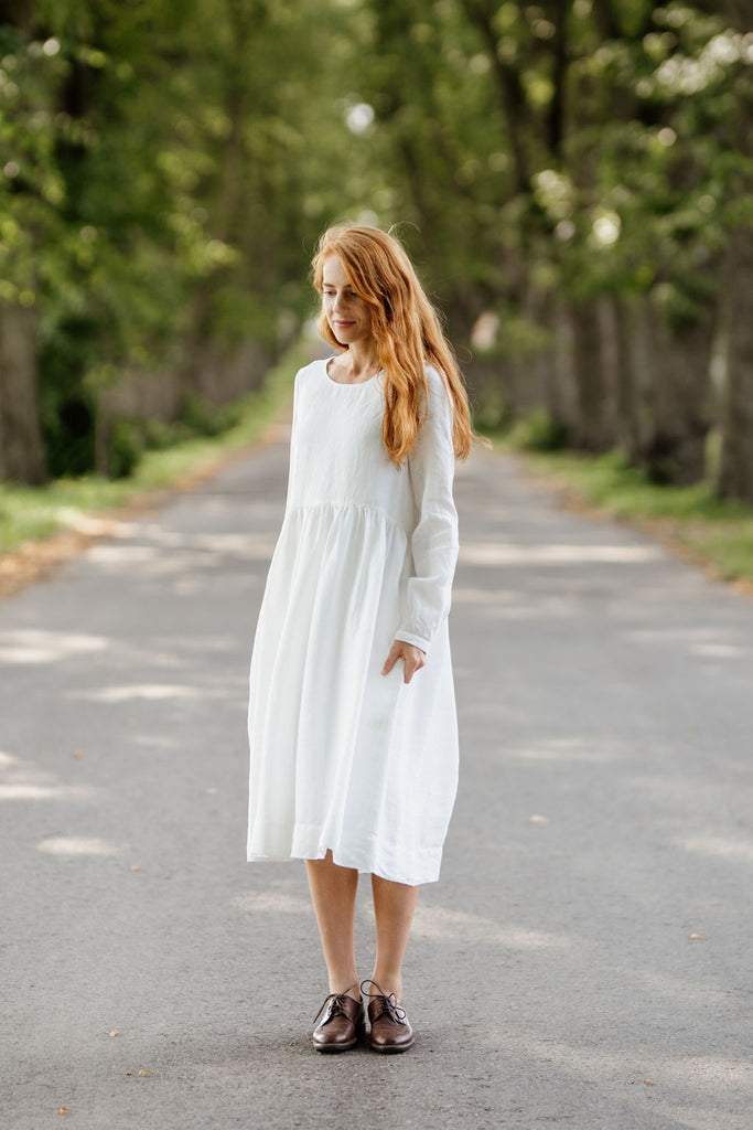 Woman wearing white smock dress with long sleeves, picture from the front