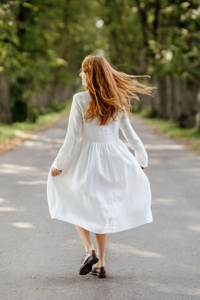 Woman wearing white smock dress with long sleeves, image from the back