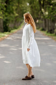 Woman wearing white smock dress with long sleeves, image from the side