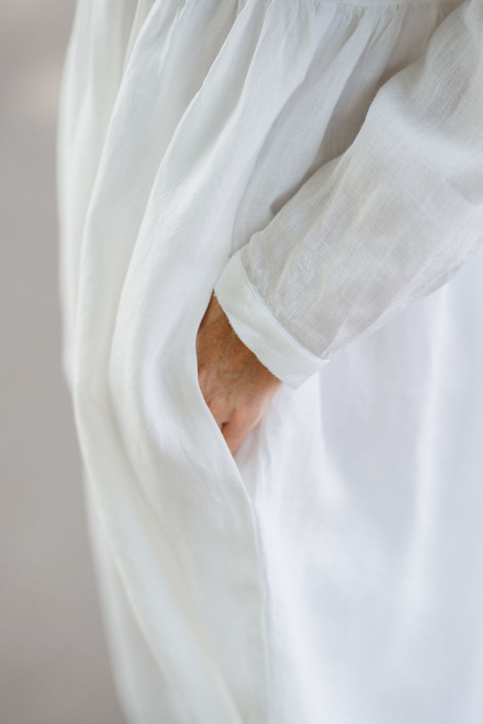 Woman wearing white smock dress with long sleeves, up close image of a pocket