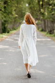 Woman wearing white smock dress with long sleeves, picture from the back