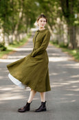 Model wearing rosemary green classic dress with long sleeves, picture from the side.