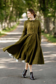 Woman wearing rosemary green classic dress with long sleeves, picture from the front.