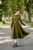 Model wearing rosemary green classic dress with long sleeves, image from the front.