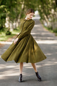 Model wearing rosemary green classic dress with long sleeves, picture from the front.