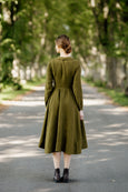 Model wearing rosemary green classic dress with long sleeves, picture from the back.