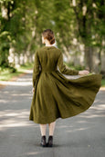 Woman wearing rosemary green classic dress with long sleeves, picture from the back.