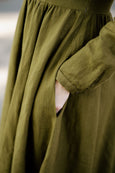 Woman wearing rosemary green classic dress with long sleeves, up-close image of a pocket from the side.