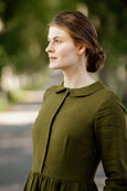 Woman wearing rosemary green classic dress with long sleeves, up-close image from the side.