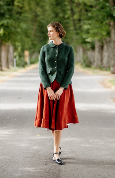 Woman wearing green linen classic jacket and red linen midi skirt