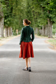 Woman pictured from the back in green linen jacket and red linen skirt