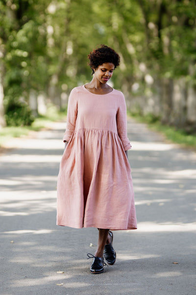 Woman wearing rose color smock dress with long sleeves, picture from the front.