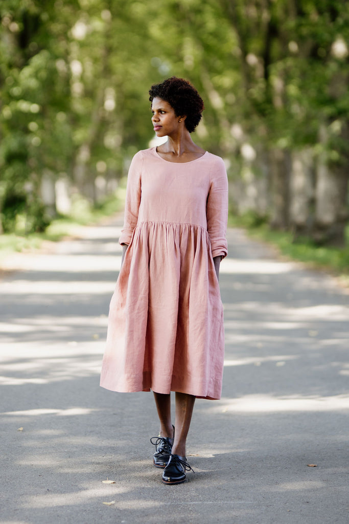 Model wearing rose color smock dress with long sleeves, picture from the front.