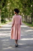 Woman wearing rose color smock dress with long sleeves, picture from the back.