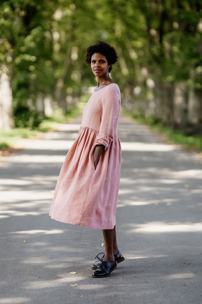 Woman wearing rose color smock dress with long sleeves, picture from the side.