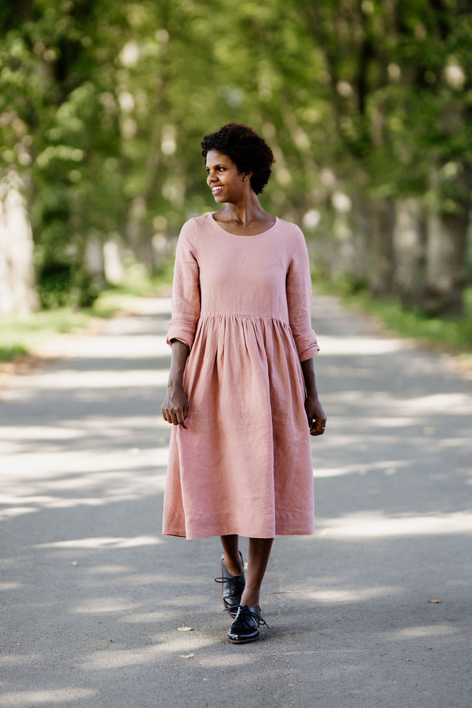 Woman wearing rose color smock dress with long sleeves, image from the front.