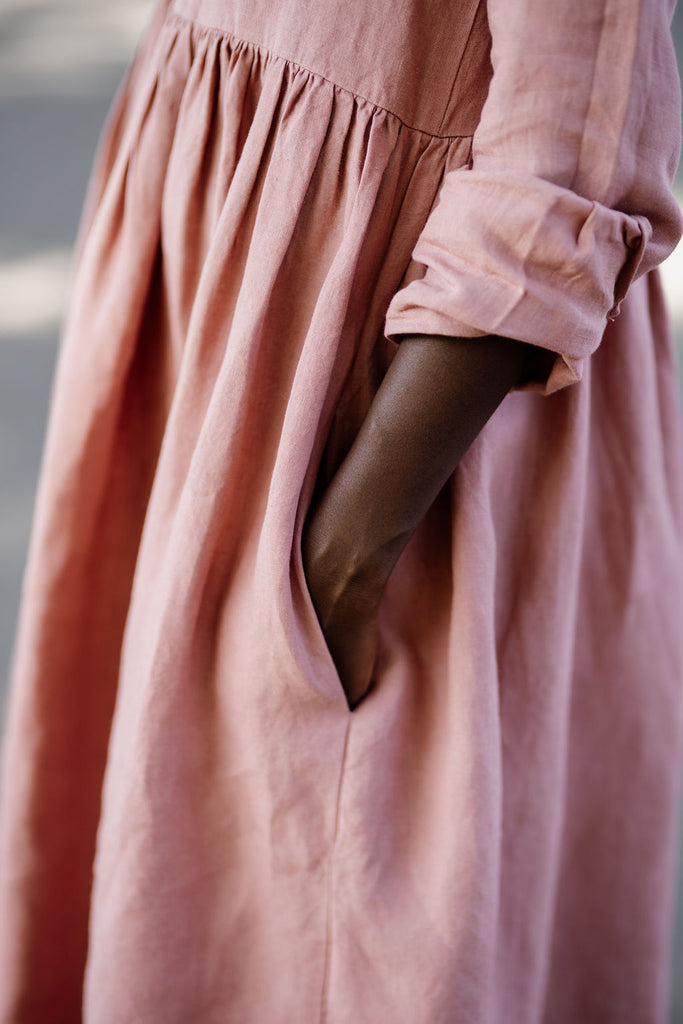 Woman wearing rose color smock dress with long sleeves, up close image of a pocket.
