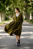Woman wearing rosemary green wrap dress with long sleeves, picture from the front.