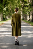 Woman wearing rosemary green wrap dress with long sleeves, picture from the back.