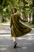 Model wearing rosemary green wrap dress with long sleeves, picture from the back.