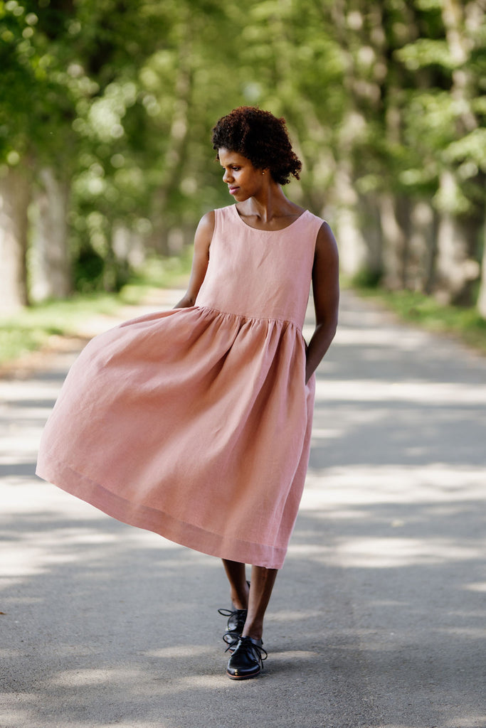 Woman wearing rose color sleeveless smock dress, image from the front.