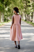 Woman wearing rose color sleeveless smock dress, image from the back.