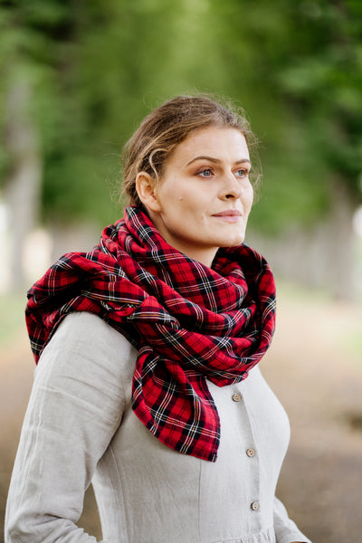 Woman wearing red tartan linen scarf and natural linen dress