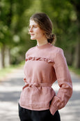 Woman wearing pink color ruffle linen shirt, image from the front
