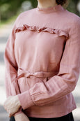 Woman wearing pink color ruffle linen shirt, up close image from the front