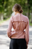 Woman wearing pink color ruffle linen shirt, image from the back