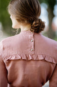 Woman wearing pink color ruffle linen shirt, up close image from the back