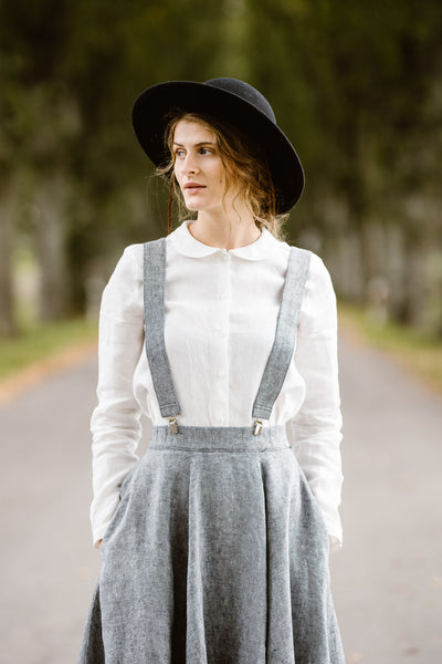 Woman wearing twill linen suspenders with adjustable clip-end, image from the front.