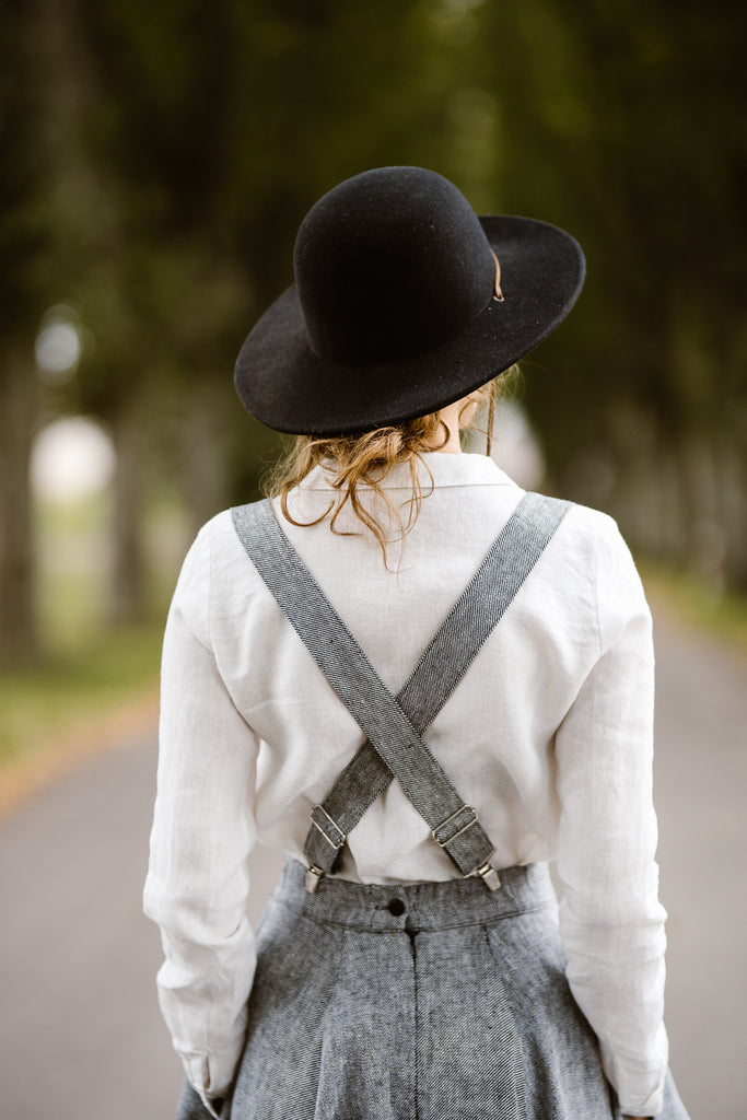 Woman wearing twill linen suspenders with adjustable clip-end, image from the back.