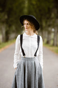 Woman wearing black color linen suspenders with adjustable clip-end, picture from the front.