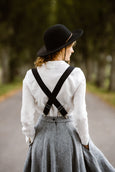 Woman wearing black color linen suspenders with adjustable clip-end, picture from the back.