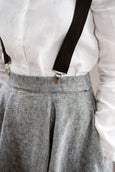 Woman wearing black color linen suspenders with adjustable clip-end, up-close image from the front.