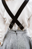 Woman wearing black color linen suspenders with adjustable clip-end, up-close image from the back.