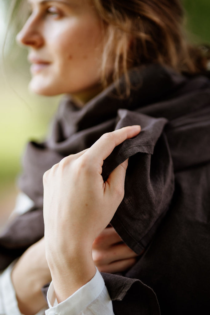 Woman wearing autumn brown shawl, up-close image from the side.