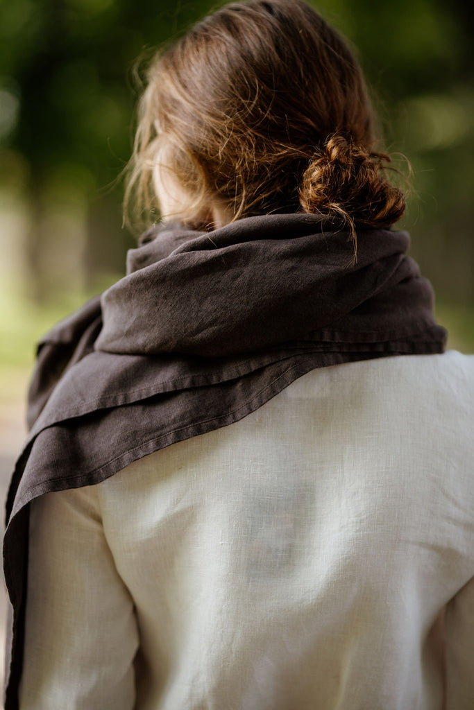 Woman wearing autumn brown shawl, image showing the back side.