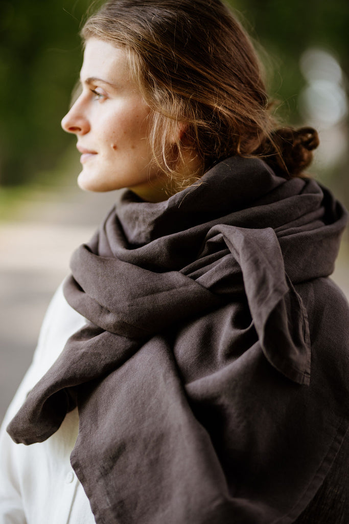 Woman wearing autumn brown shawl, image from the side.