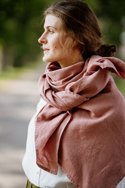 Woman wearing rose color shawl, image from the side.
