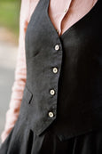 Woman wearing black linen vest, up close image from the front