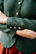 Emerald green linen blazer with coconut buttons, up close image of a sleeve