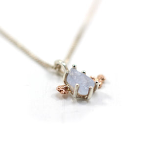 Pale blue rough sapphire set in sterling silver with gold nuggets either side